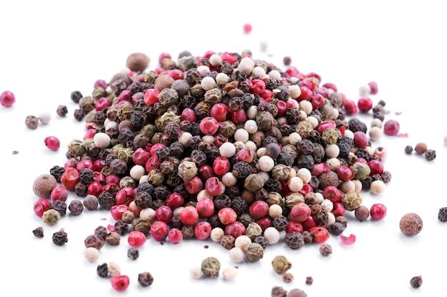 Haufen von schwarzen, roten und weißen pfefferkörnern auf weißem tisch isoliert mit kopienraum, draufsicht. lebensmittelhintergrund