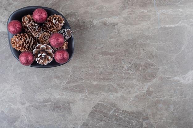 Haufen von tannenzapfen und weihnachtskugeln in einer schüssel auf marmoroberfläche