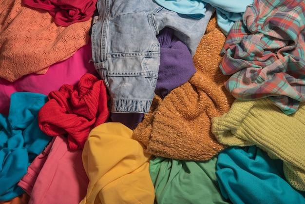 Haufen von unvorsichtig verstreuten kleidern.