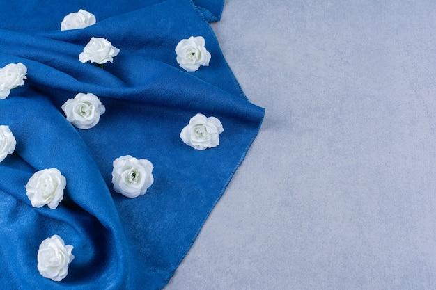 Haufen weißer rosen auf blauem stoff auf stein verstreut.