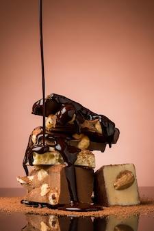 Haufen zerbrochener schokolade auf dem tisch vor braunem studiohintergrund und heißem schokoladenspray
