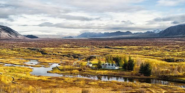 Haukadalur-tal in island. kleine gebäude in ruhiger naturumgebung. tallandschaft sonniger herbsttag bewölkter himmel. erstaunliche schönheit des tals. schöne landschaft mit fluss im tal.