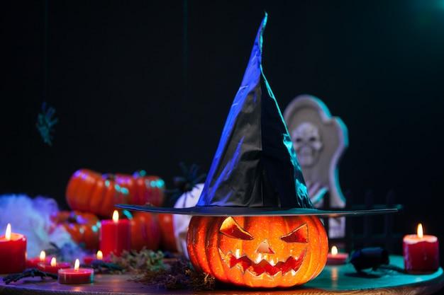 Haunted hexenkürbis mit einem großen schwarzen hut bei der halloween-feier. halloween-dekoration.