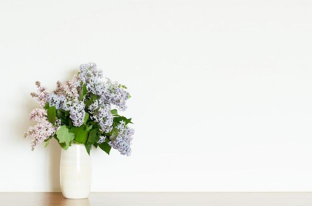Hauptdekor, lila blumen im vase auf einem weißen wandhintergrund. innere.