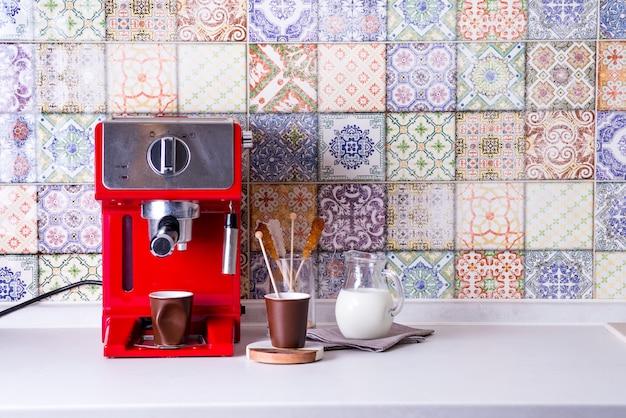 Hauptespressomaschine auf küchenarbeitsplatte mit zwei schalen, milch und zucker auf stöcken. kaffee kochen zu hause.