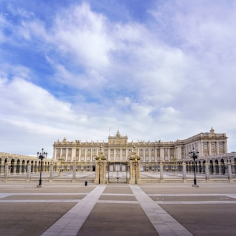 Hauptfassade des königlichen palastes von madrid mit seiner riesigen esplanade und dem blauen himmel mit wolken bei sonnenaufgang. spanien.