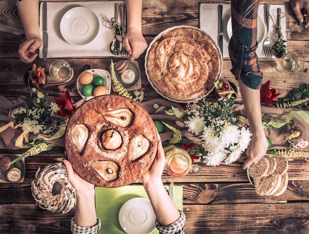 Hauptfeier von freunden oder familie am festlichen tisch mit birnenkuchen, draufsicht, feierkonzept