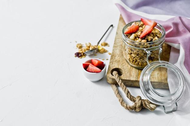 Hauptgranola mit erdbeeren in einem glasgefäß.
