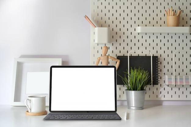Hauptschreibtisch mit tablette des leeren bildschirms mit intelligenter tastatur auf minimaler arbeitsplatztabelle.