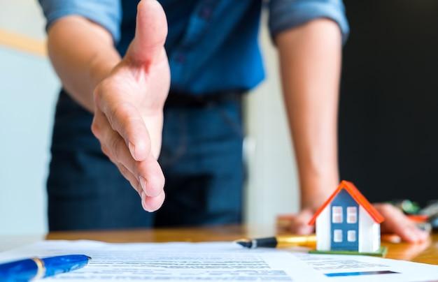 Hauptverkäufer dehnt aus, um hände, feder und modellhaus auf hausplan zu rütteln.