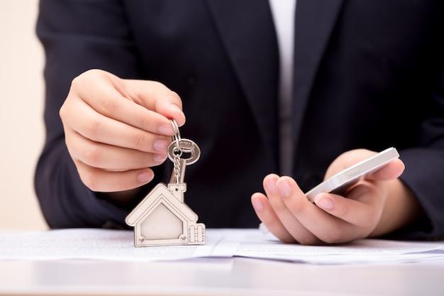 Hauptverkäufer, der hauptschlüssel hält. konzept für das immobiliengeschäft.