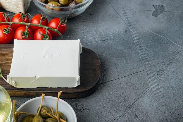 Hauptzutaten des griechischen salats, frische olivenmischung, feta-käse, tomaten, auf grauem hintergrund mit kopienraum für text