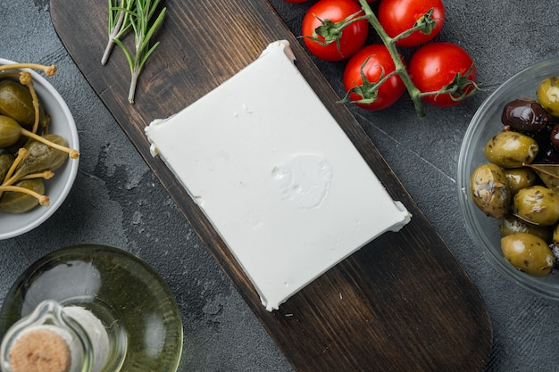 Hauptzutaten des griechischen salats, frische olivenmischung, feta-käse, tomaten, auf grauer, flacher lage