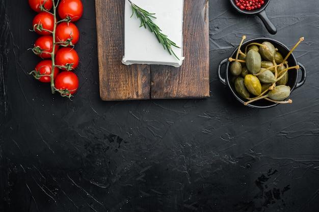 Hauptzutaten des griechischen salats, frische olivenmischung, feta-käse, tomaten, auf schwarz, draufsicht