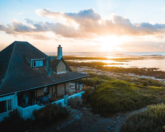 Haus am wasser am strand mit einer wunderschönen untergehenden sonne am horizont