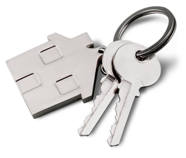 Haus geformter schlüsselanhänger und schlüssel isoliert auf weißem hintergrund