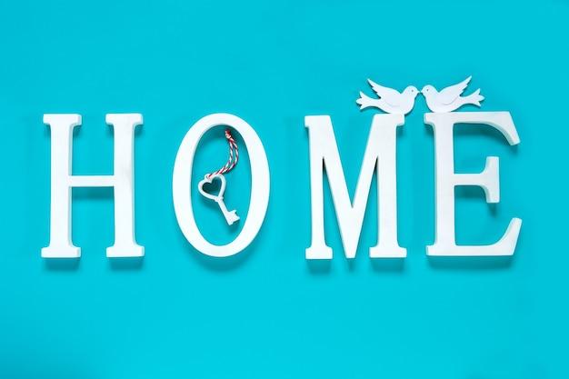 Haus, holztext mit herzformdekor auf blauem hintergrund. konzept des bauens von häusern, der wahl ihres eigenen hauses, der hypothek, des kaufs, des verkaufs von wohngebieten, der vermietung, der versicherung, der anlageimmobilien.