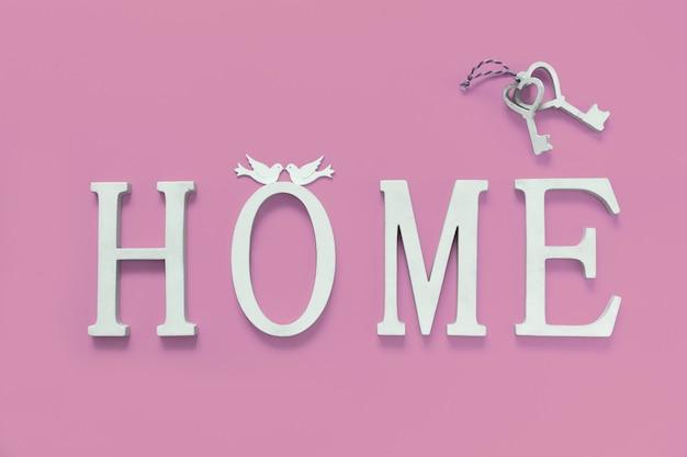 Haus, holztext mit herzformdekor auf rosa hintergrund. konzept des bauens von häusern, der wahl ihres eigenen hauses, der hypothek, des kaufs, des verkaufs von wohngebieten, der vermietung, der versicherung, der anlageimmobilien.