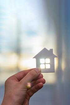 Haus in der hand, in den strahlen der sonne. konzept zum schutz des eigentums. platz für text.