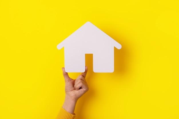 Haus in der hand über gelbem hintergrund, versicherungskonzept