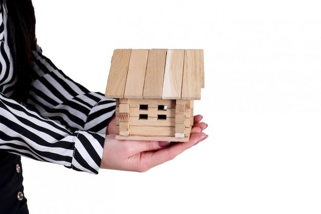 Haus in menschlichen händen auf einer weißen wand
