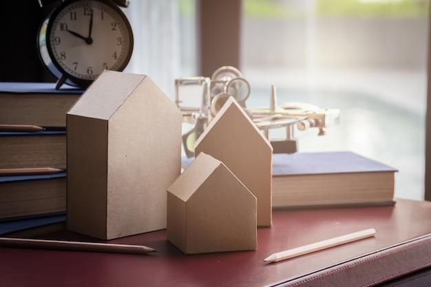 Haus karton modell mit buch und wecker mit unschärfe hintergrund
