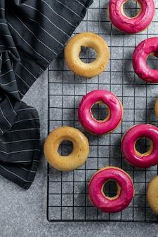 Haus machte backenkonzept - frische gebackene schaumgummiringe mit heller rosa zuckerglasur auf abkühlendem gestell