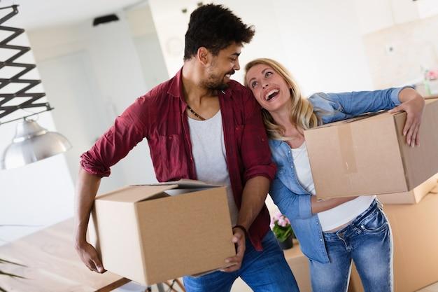 Haus-, menschen-, umzugs- und immobilienkonzept - glückliches paar, das spaß beim einzug in eine neue wohnung hat