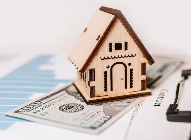Haus miniaturmodell und geld für dokumente. investition, immobilien, haus, wohnen