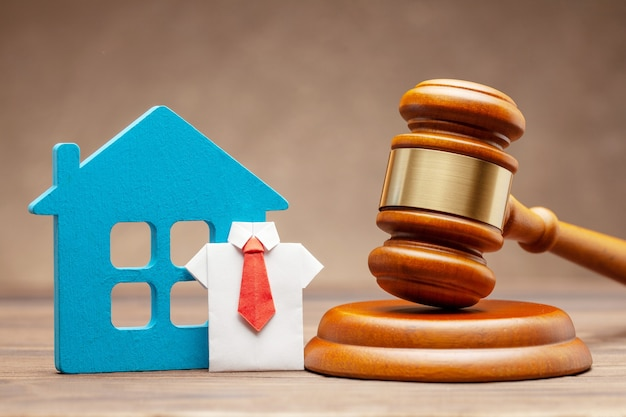 Haus mit geschäftsmann in hemd und krawatte und richterhammer auf brauner oberfläche. konzept des verkaufs eines hauses durch auktion oder satz von recht.