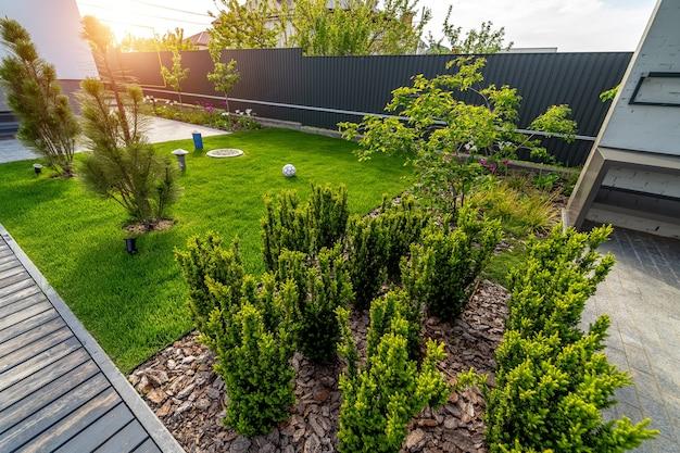 Haus mit herrlicher außenlandschaft. grünes gras und schöne kleine bäume.
