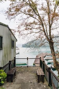 Haus mit holzsitzen und bäumen in der nähe der seilbahnstation sun moon lake in der gemeinde yuchi