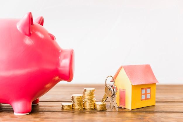 Haus mit schlüssel und gestapelten münzen neben sparschwein
