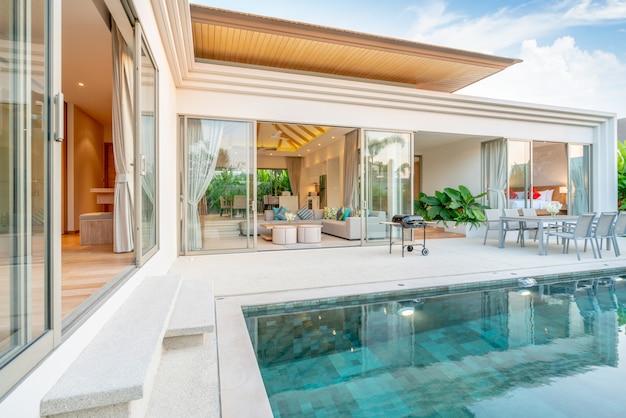 Haus oder haus außendesign mit tropischer poolvilla mit begrüntem garten, sonnenliegen, sonnenschirm und badetüchern