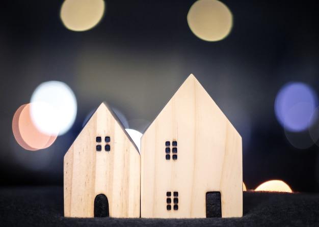 Haus- oder hausholzmodell für familienglückskonzept mit bokeh-licht von der modernen innenstadtstadt