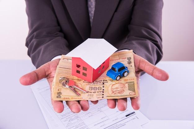 Haus- und autokaufkonzept, indischer mann, der indische währung in beiden händen hält und modellhaus und spielzeugauto darüber, nahaufnahme und selektiver fokus