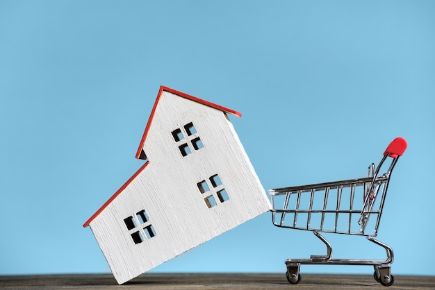 Haus und einkaufswagen. hauskonzept kaufen. vorderansicht des blauen hintergrunds.