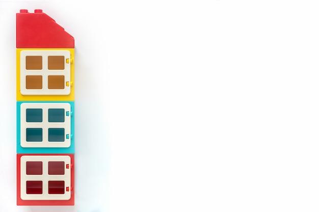 Haus von plastikerbauerziegelsteinen auf weißem hintergrund. beliebtes spielzeug. freier platz für text