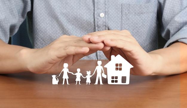 Haus wohnstruktur in der hand, geschäftshausidee, die schutzpapierkettenfamilie zeigt