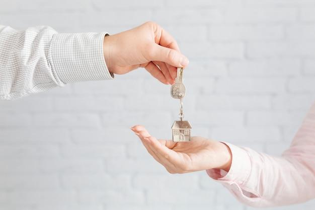 Hausagent, der dem kunden schlüssel gibt
