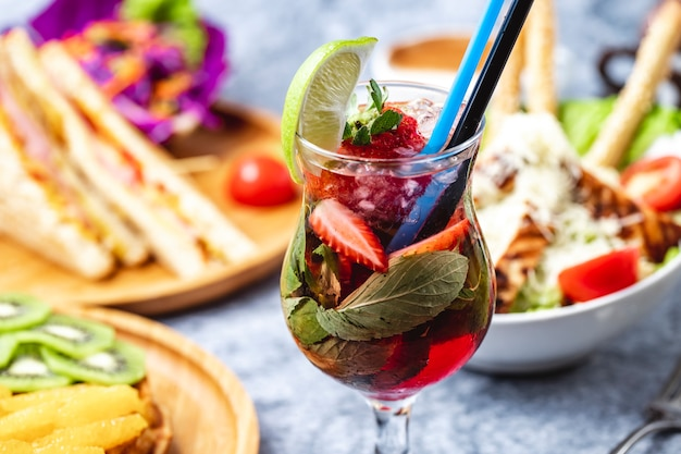 Hausansicht hausgemachte limonade mit erdbeerscheibe von zitrone und minze im glas