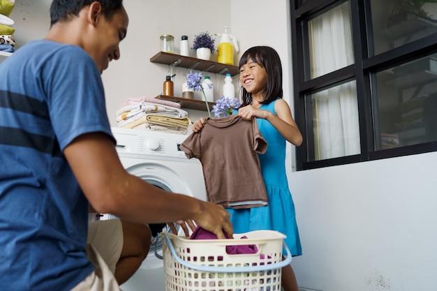 Hausarbeit. asiatischer mann, der wäsche zu hause beim laden von kleidung in die waschmaschine macht