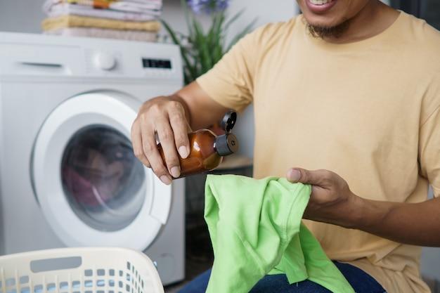 Hausarbeit. asiatischer mann, der wäsche zu hause macht. tragen sie etwas reinigungsmittel auf die kleidung auf