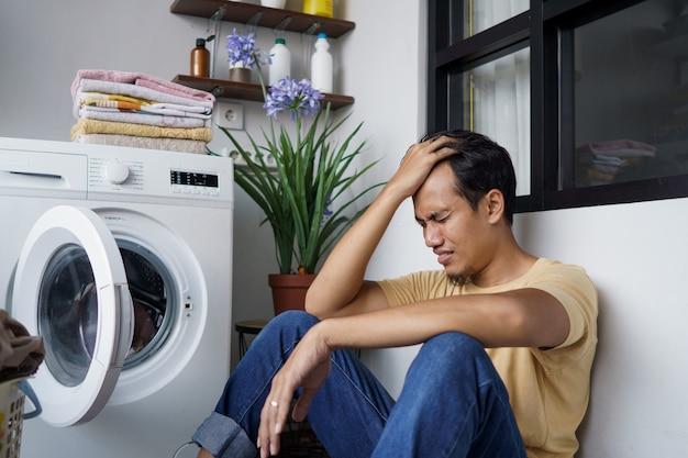 Hausarbeit. gestresster asiatischer mann, der wäsche zu hause beim laden von kleidung in die waschmaschine macht
