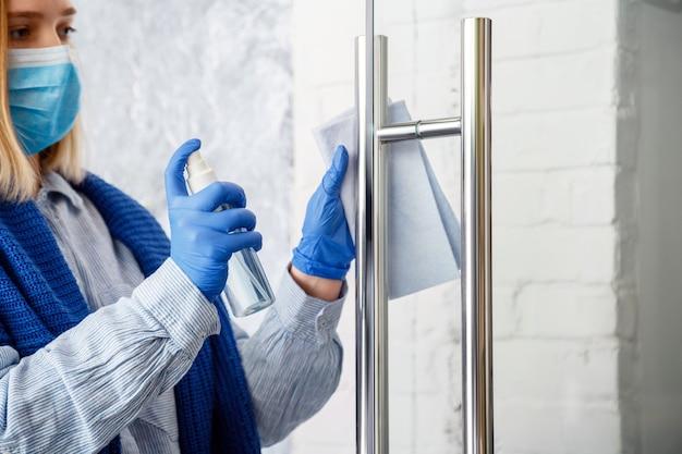 Hausarbeiterinnenporträt in blauen gummihandschuhen reinigen türknauf mit stofflappen, der den türgriff mit antibakteriellem alkoholspray reinigt, neues normales covid-coronavirus bei der oberflächendesinfektion