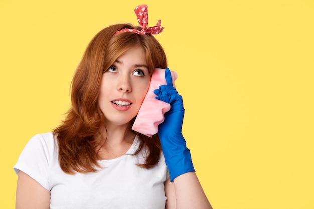 Hausarbeitskonzept. hübsche junge beschäftigte hausfrau gibt vor, über smartphone zu kommunizieren, verwendet schwamm