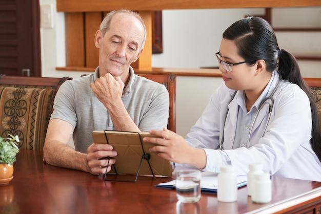 Hausarzt, der dem älteren patienten testergebnisse auf tablet-pc zeigt