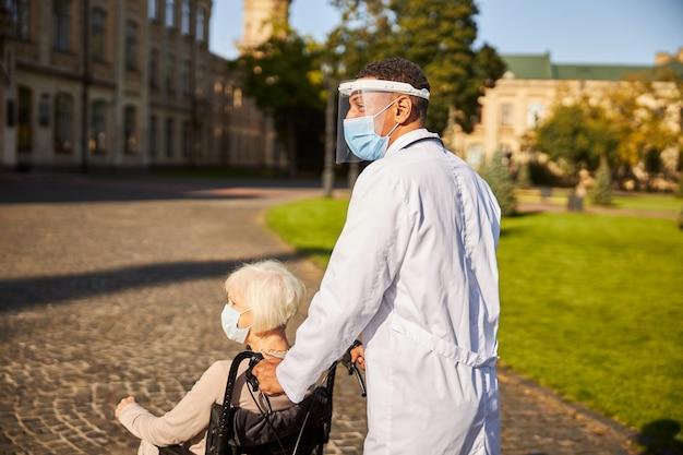 Hausarzt in einem schutzschild auf seinem gesicht, der einen rollstuhl einer alten frau führt