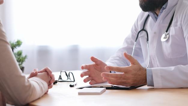 Hausarzt und patient sprechen in arztpraxis.