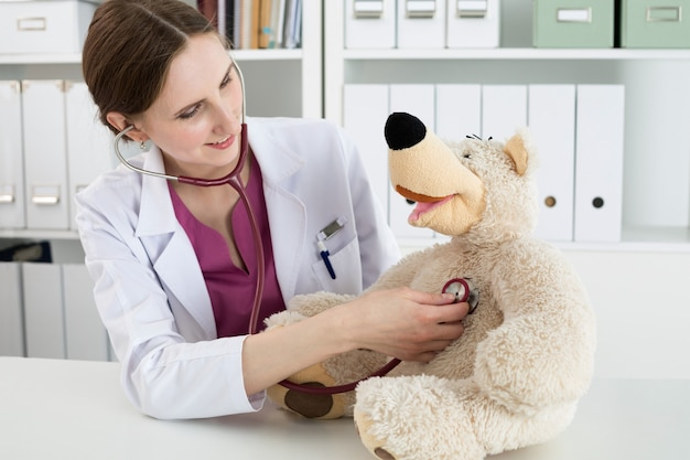 Hausarztuntersuchung. schöne lächelnde ärztin im weißen kittel untersuchen teddybär mit stethoskop, um kind zu beruhigen und zu interessieren. mit babypatienten spielen. pädiatrisches medizinisches konzept